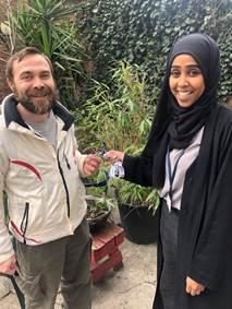 Iulian receiving the keys to his new home from hub worker, Zainab