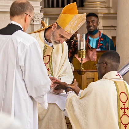 Bishop anoints hands with Oil of Chrism