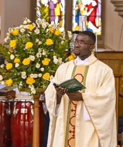 Fr Paschal beside flowers