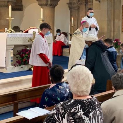 Bishop holds hand above parishioner