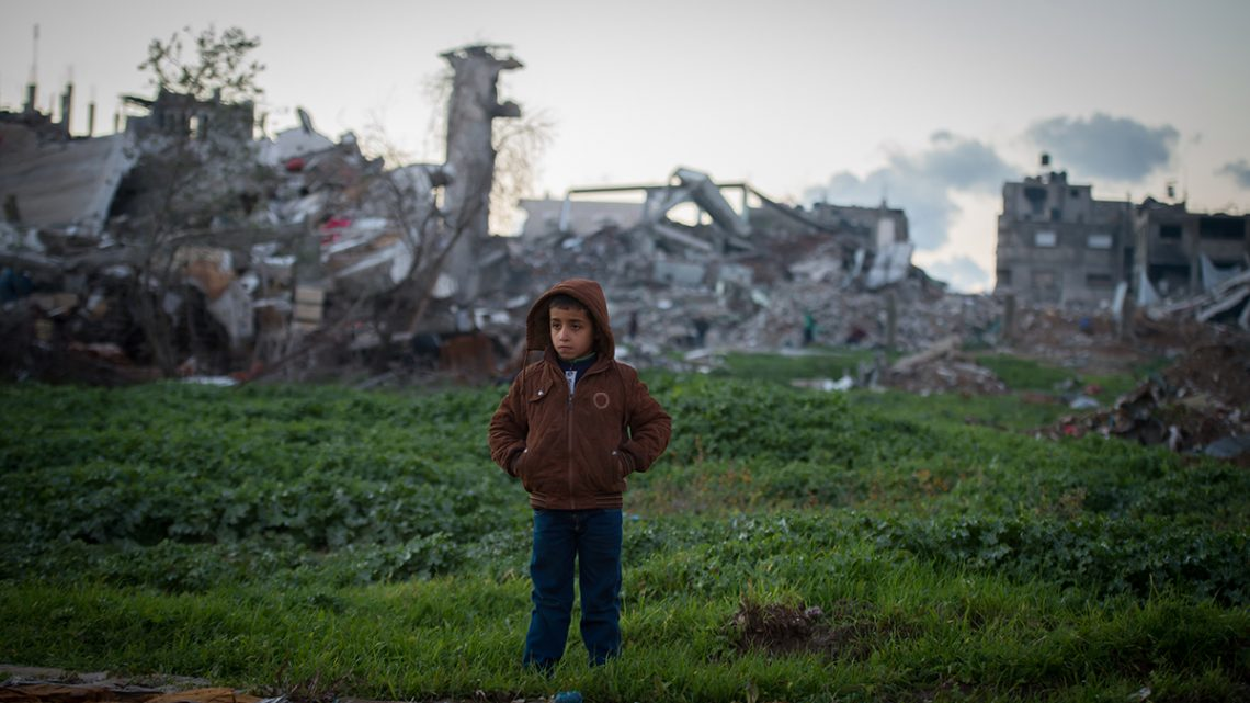Boy in front of bombed buildings