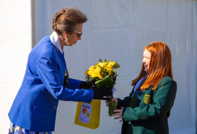 Girl handing flowers to Princess Royal